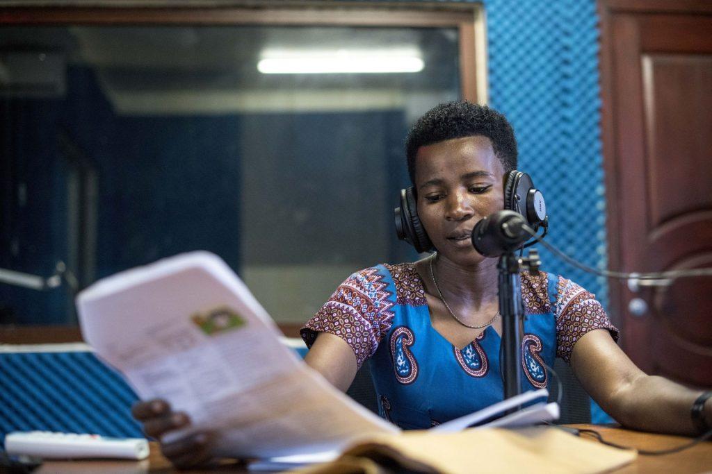 Nainen puhuu mikrofoniin studiossa kuulokkeet korvilla.