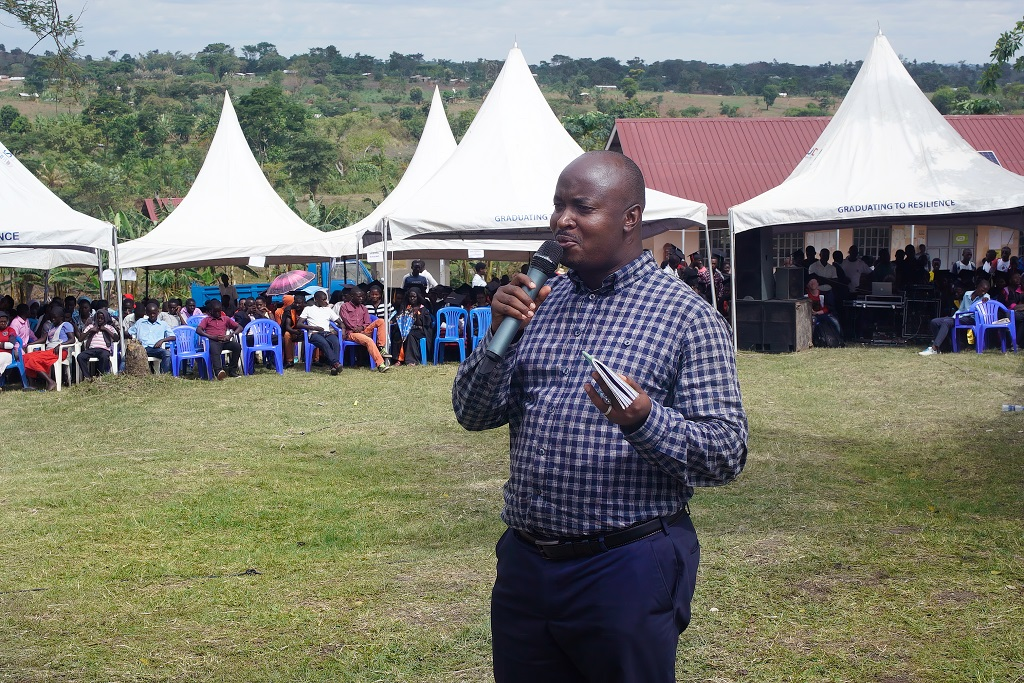 Mies puhuu mikrofoniin ruohokentällä, yleisöä ja valkoisia telttakatoksia taustalla.