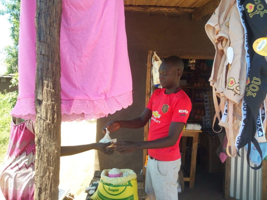 Alex Lojuan attending to a customer at his Retail shop located in Odraji Village, Zone 1 – Palorinya settlement