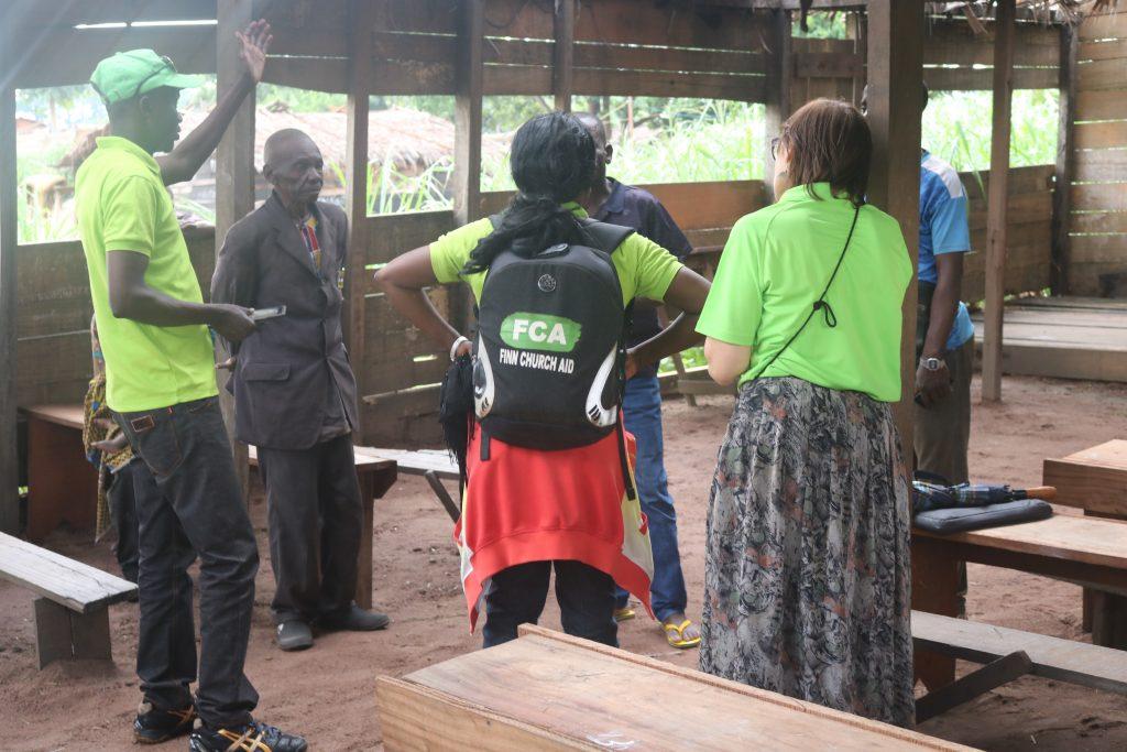 Joukko aikuisia, joista puolilla KUA:n paita, keskustelee ringissä luokkahuoneessa.