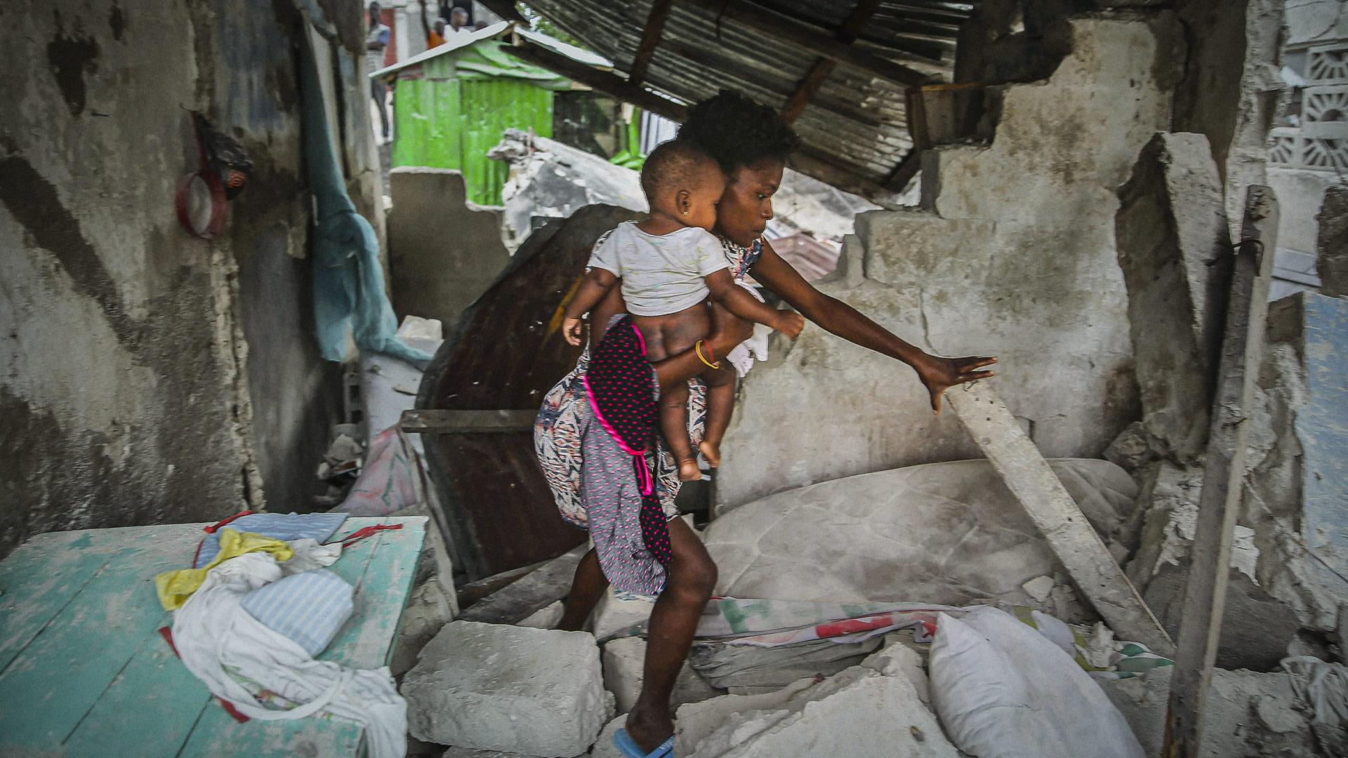 En haitisk mor med sitt barn i famnen i ett hus som delvis rasat. Bilden är från AP/Lehtikuva.