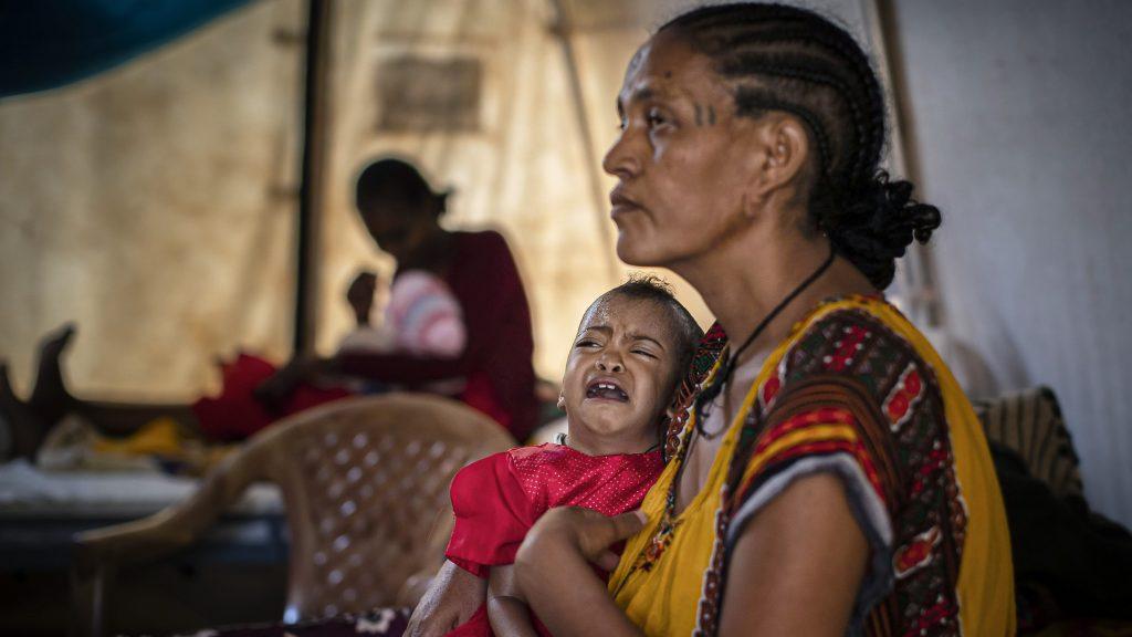 Äiti pitää sylissä aliravittua tytärtään klinikan hoitoteltassa Tigrayn alueella Etiopiassa