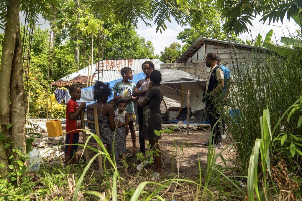 Nainen istuu penkillä lapset ympärillään. Taustalla sortuneita rakennuksia Haitissa.