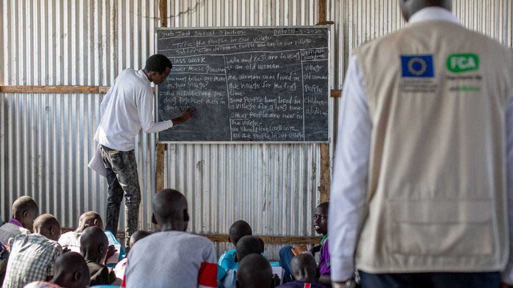 Opettajaharjoittelija seuraa opettajan työtä liitutaulun äärellä.
