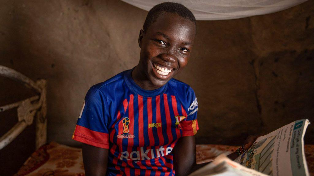 Tyttö hymyilee kameralle kotonaan Etelä-Sudanissa.