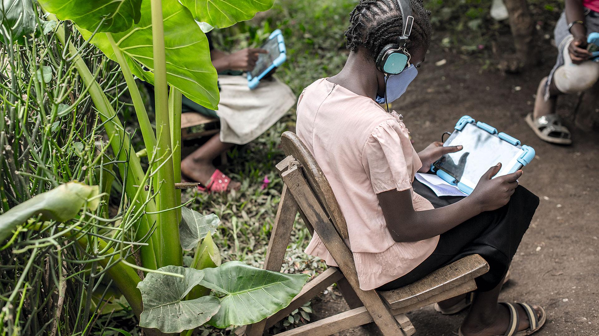 Lapsi käyttää taulutietokonetta kuulokkeet korvilla.