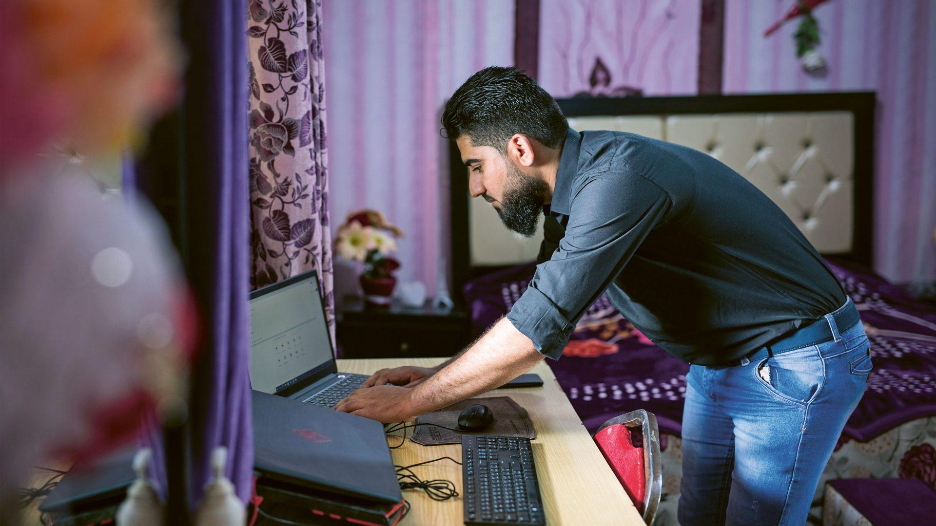 Mies näppäilee tietokonetta.
